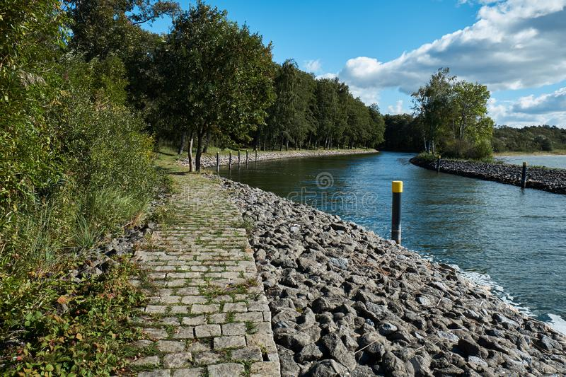 Cobblestone path near a waterway leading from a lake to a marina with a forest to the left. stock images
