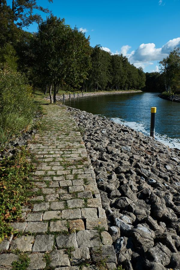 Cobblestone path near a waterway leading from a lake to a marina with a forest to the left. Vertical shot.  royalty free stock photo