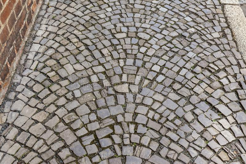 Cobblestone path with random pattern. Cobblestone footpath along brick wall with interesting pattern. Ideal as background stock photos