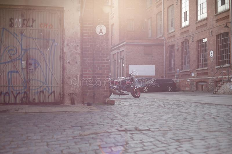 Cobblestone paved court of an old industrial area with brick wall buildings in bright sunlight - vintage urban flair concept - for. An old european industrial royalty free stock photos