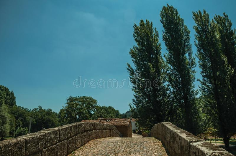 Cobblestone pavement over an old Roman bridge in Portagem. Cobblestone pavement and breastwork over an old Roman bridge still in use over the Sever River among stock photo