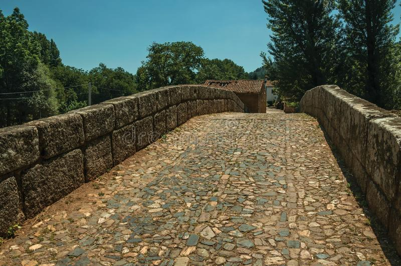 Cobblestone pavement over an old Roman bridge in Portagem. Cobblestone pavement and breastwork over an old Roman bridge still in use over the Sever River among stock photos