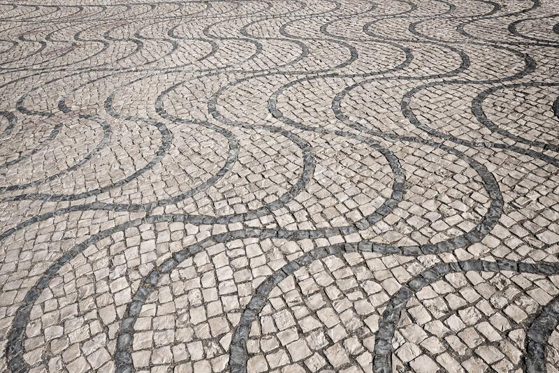 Cobblestone pavement with wavy lines, made of granite cubes. black and white. Cobblestone pavement with wavy lines, made of granite cubes. historic street paving stock photography
