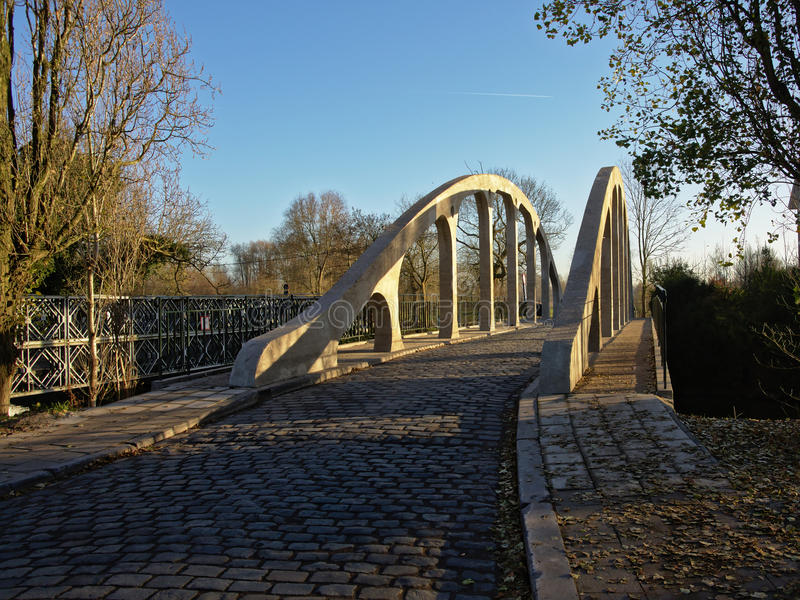 Cobblestone road over old tied arch bridge in Drongen, Flanders. Cobblestone road over old tied arch bridge in the Flemish countryside stock image