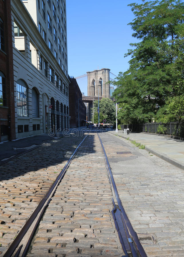 Cobblestone street with abandoned train track and Brooklyn Bridge view. BROOKLYN, NEW YORK - AUGUST 13, 2017: Cobblestone street with abandoned train track and royalty free stock photo