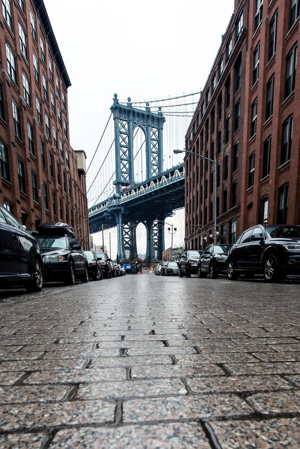 Cobblestone street in Brooklyn. Cobblestone street alley and red brick buildings in Brooklyn with Manhattan Bridge in background royalty free stock images