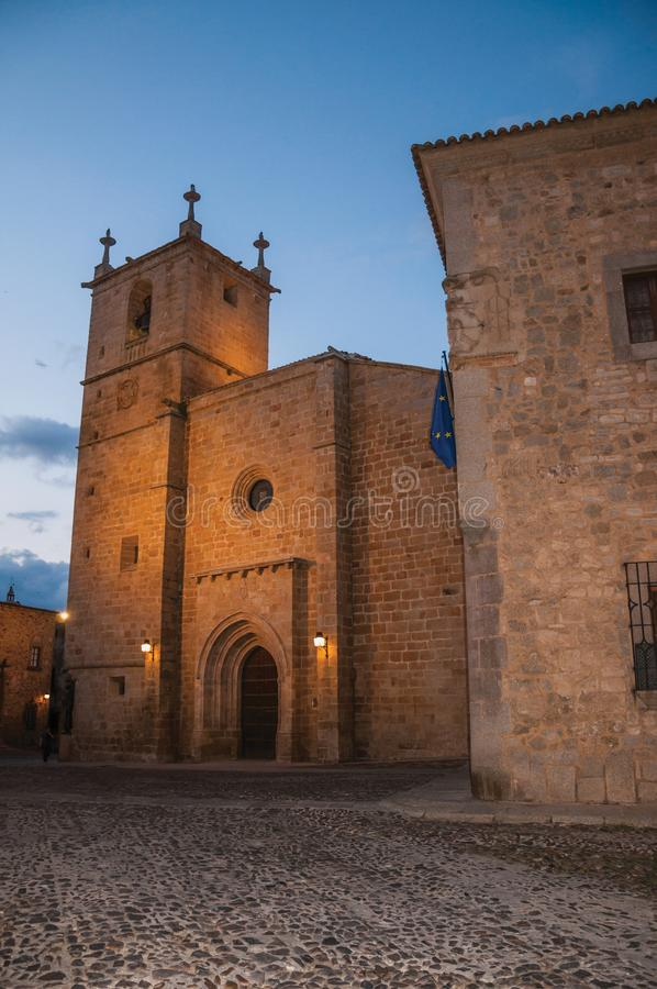 Cobblestone street with church and gothic buildings at dusk in Caceres royalty free stock photography
