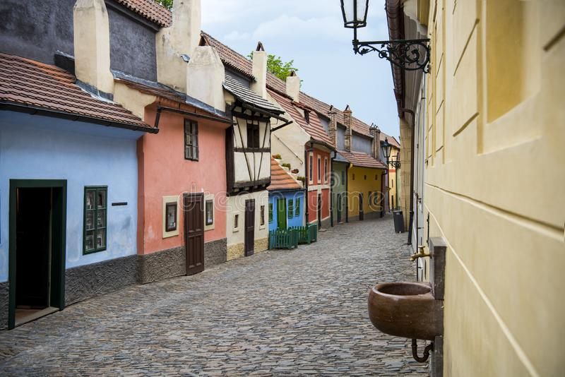 Cobblestone street and colorful 16th century cottages of artisans known as Golden Lane inside the castle walls Prague Czech Re royalty free stock photo