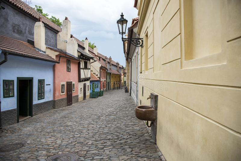 Cobblestone street and colorful 16th century cottages of artisans known as Golden Lane inside the castle walls Prague Czech Re royalty free stock image