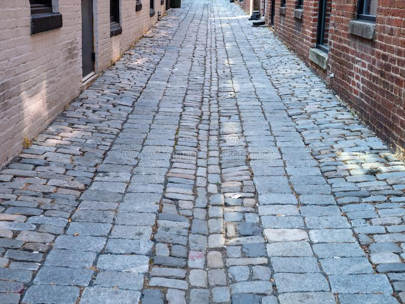 Cobblestone street in the daytime moving through a brick alleyway. A cobblestone street in the daytime moving through a brick alleyway stock photography