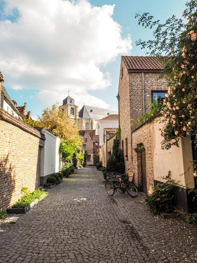 Cobblestone street leading to the beguinage church in the large royalty free stock photography