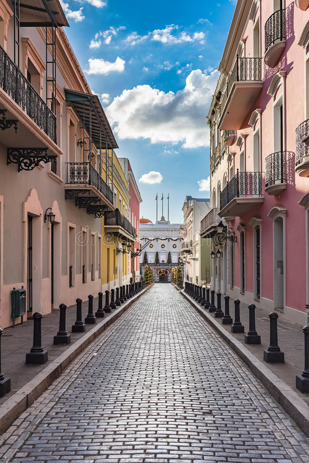 Cobblestone street of old town leading to historic building. La Fortaleza at the end of the street stock images