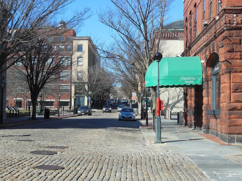 Cobblestone street on quiet winter morning. New Bedford, Massachusetts, USA - March 10, 2018: Cobblestone street on quiet winter morning in front of Freestone`s royalty free stock images
