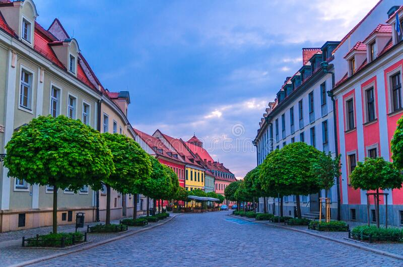 Cobblestone street road with colorful multicolored buildings and green trees in old town. Historical city centre, evening view, Ostrow Tumski, Wroclaw, Poland stock photos