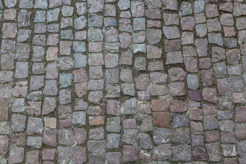 cobblestoned granittrottoar för bakgrund Stentrottoartextur Abstrakt bakgrund av den gamla kullerstentrottoarnärbilden i Prag royaltyfri foto