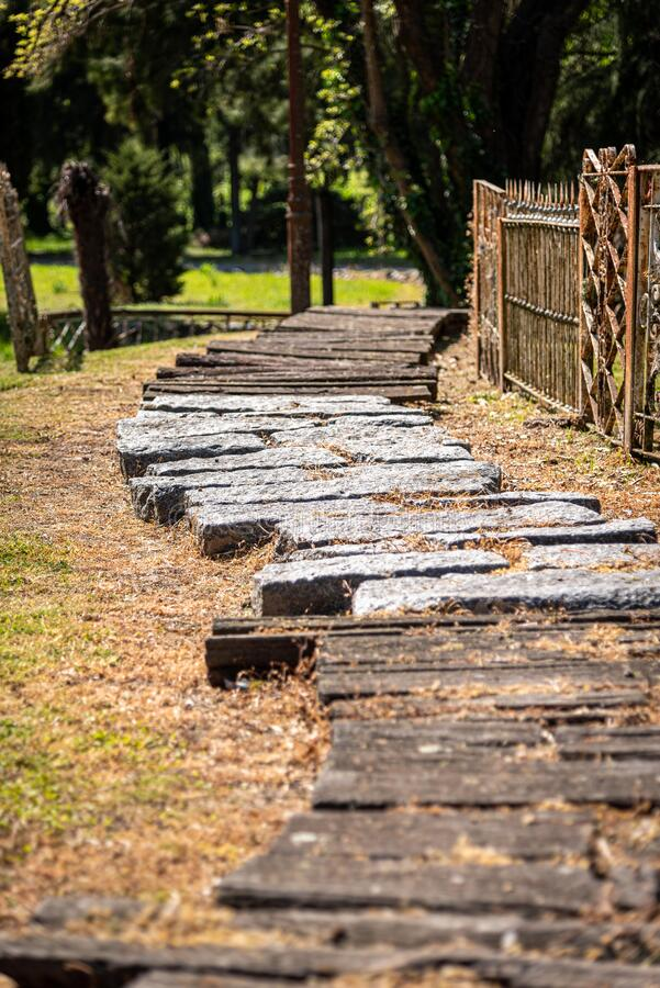 Cobblestoned and wooden curved path beside an old rusty and grungy fence in a park.  stock photography