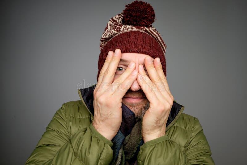 A coberta madura considerável do homem eyes com mãos quando o fundo cinzento estando no inverno morno se vestir fotos de stock royalty free