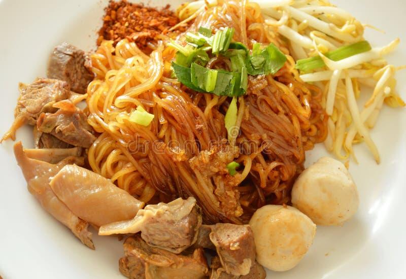 A cobertura fina secada do macarronete de arroz assou a pimenta de caiena do molho da carne de porco no prato fotos de stock royalty free
