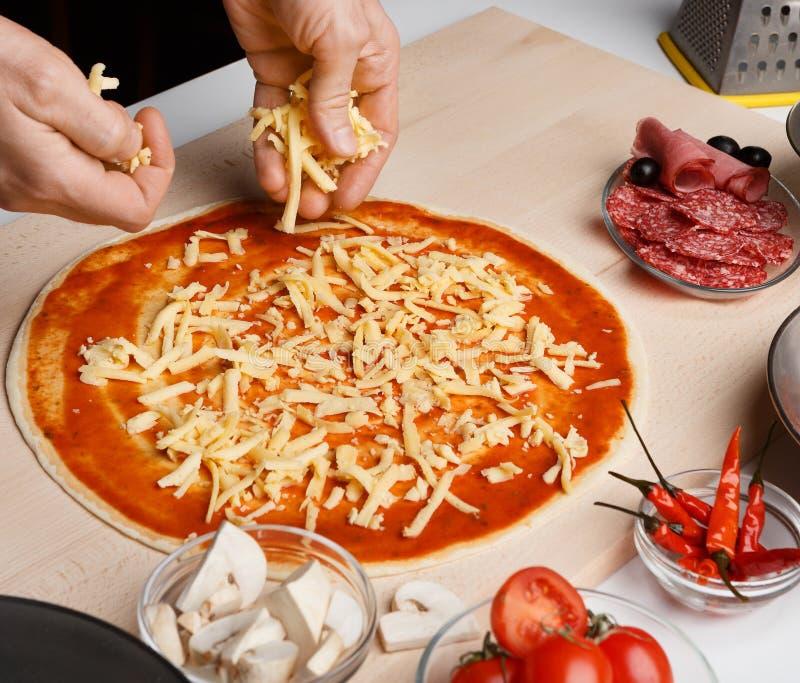 Coberturas de espalhamento do queijo do cozinheiro chefe na base da pizza imagens de stock
