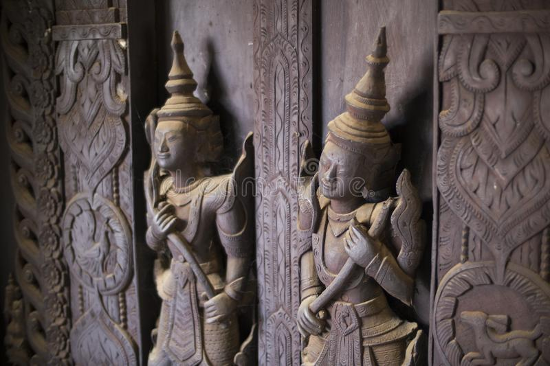 Wooden figures covered in cobweb, Shwe In Bin Kyaung monastery, Mandalay. Cobweb covered carved wooden figures and panels within the Shwe In Bin Kyaung royalty free stock image