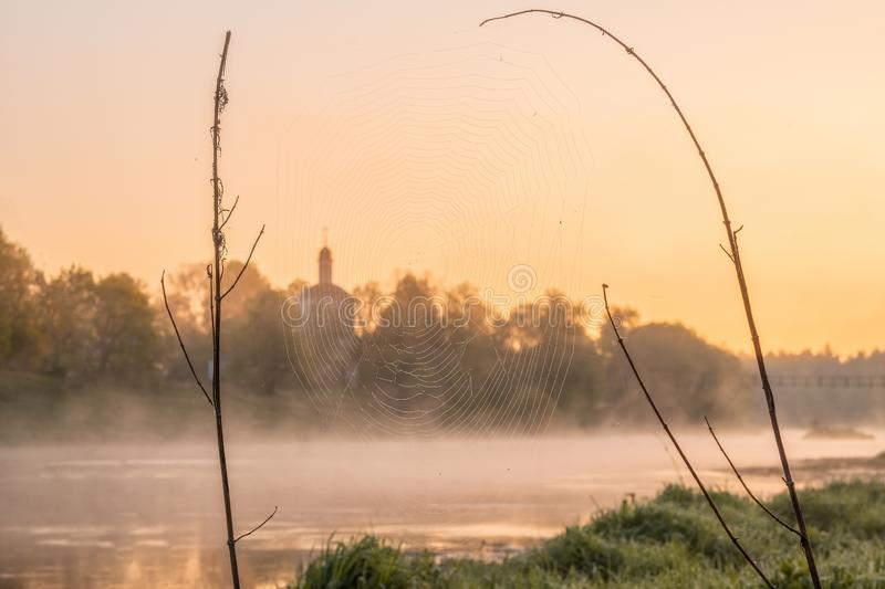A cobweb between dry grass stalks, covering up an Orthodox church against the backdrop of a rich orange dawn sky stock photo