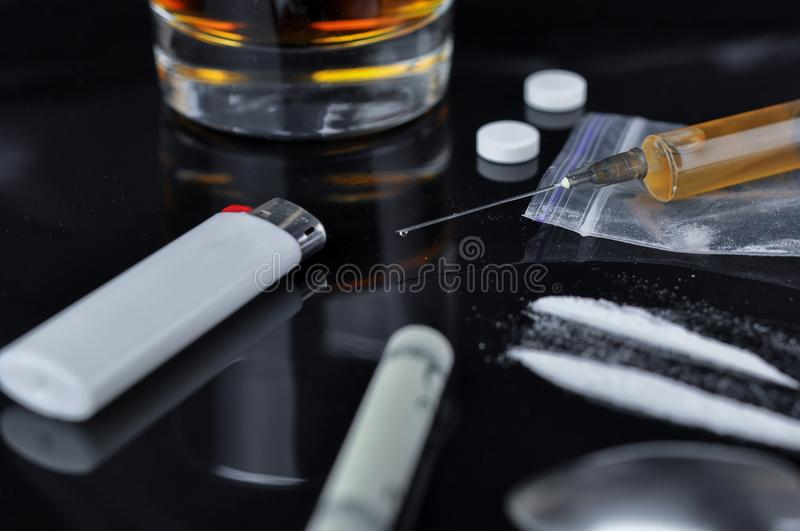 Cocaïne, pillen, alcohol en heroïne in spuit stock foto