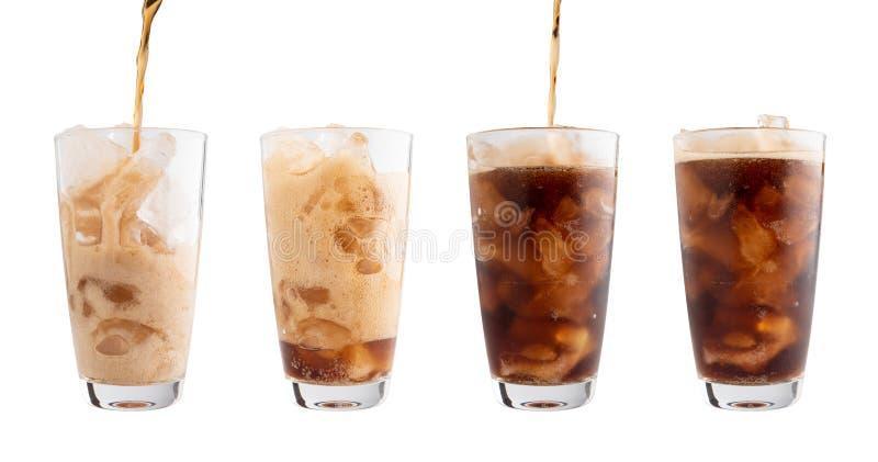 Coca Cola de versement dans le verre a isolé le fond blanc, coupant photographie stock