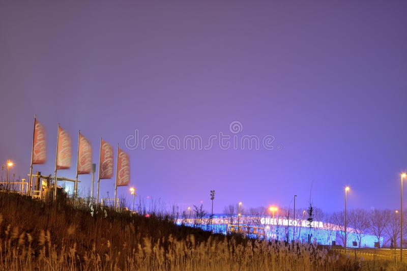 Coca Cola flags, Belgian branch in Ghent at night and ghelamco Arena football stadium. GHENT, BELGIUM, MARCH 2016:Coca Cola flags, Belgian branch in Ghent at stock photography