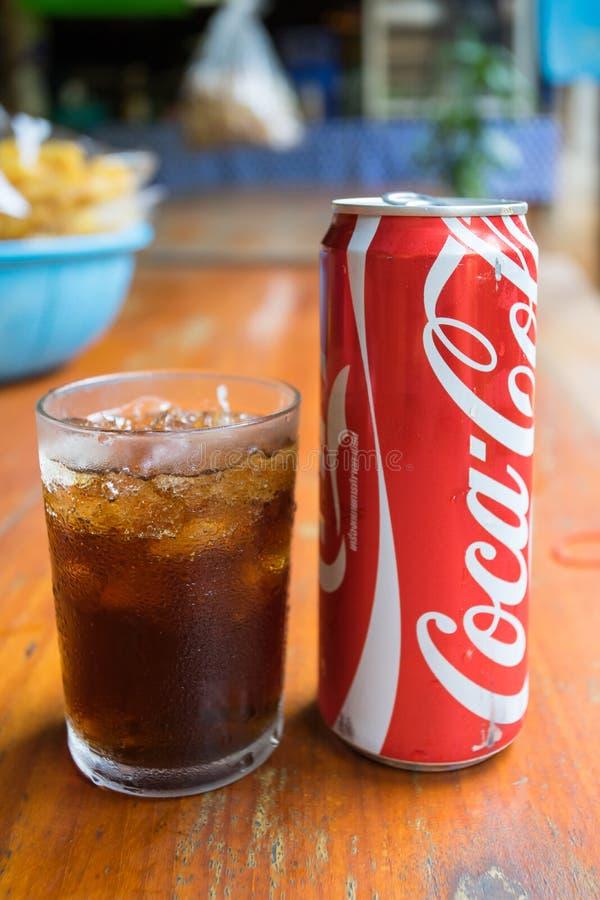 Coca - cola kan dricka och ett exponeringsglas av cola med iskuber royaltyfri foto
