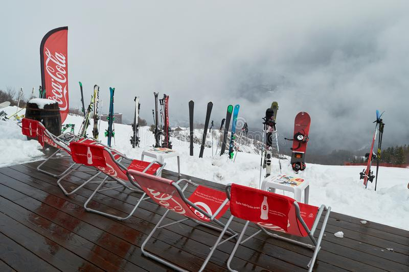 Coca Cola sun chairs on a piste apes-ski lodge terrace deck with ski/snowboard equipment in front of it stock images