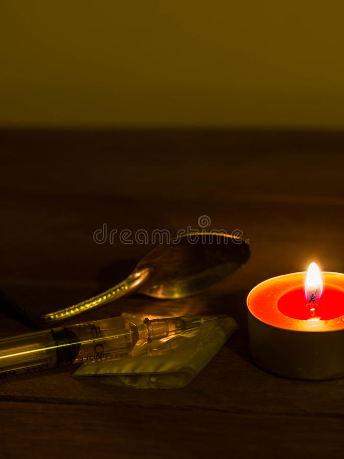 A cocaine injection needle was placed on a wooden table with a cocaine bag and a spoon of light shining down from the candle. We are against drugs anti drugs royalty free stock photography