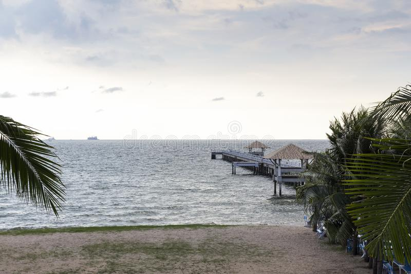 Cocco e passaggio pedonale di legno estendere al mare sulla spiaggia alla costa e sul cielo blu nella festa alla sera fotografia stock