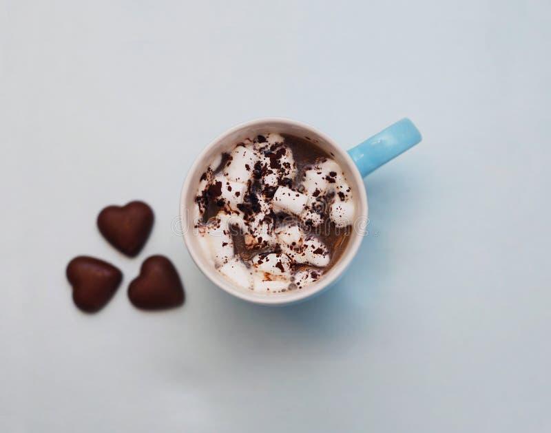 Coccoa caliente o chocolate con forma del corazón de las melcochas y de los chocolates en fondo azul entonado Concepto caliente d imágenes de archivo libres de regalías