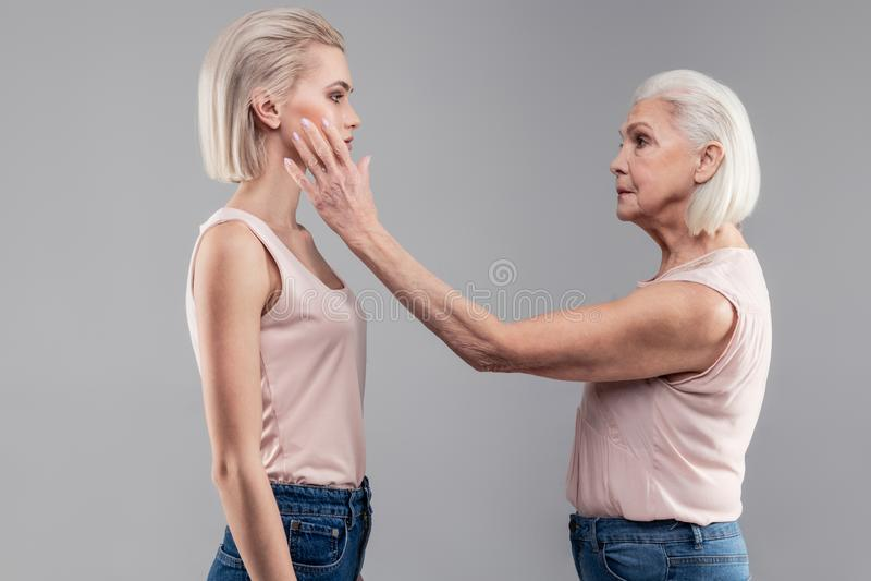Coccole senior ordinate serie di signora la sua giovane versione dai capelli corti immagini stock