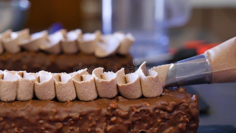 Cocer una torta Exprimir la crema en la torta Crema deliciosa deliciosa exprimida en la torta fotos de archivo libres de regalías