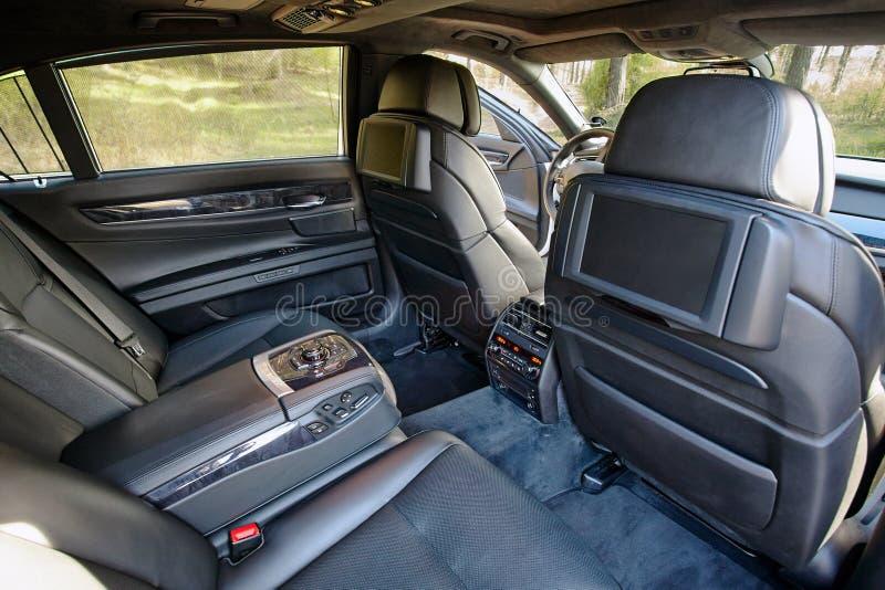 Coche adentro Interior del coche moderno de lujo del prestigio Dos exhibiciones para el pasajero de los asientos traseros con el  imagen de archivo libre de regalías