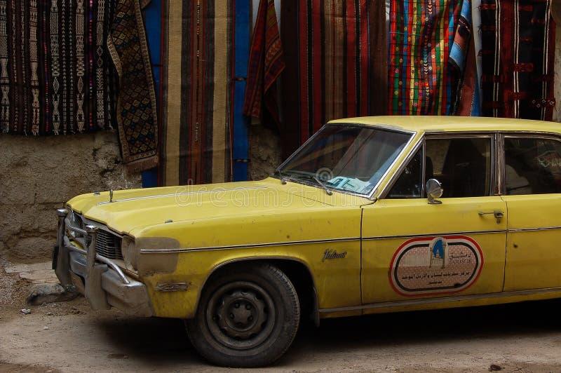 Coche amarillo con en el fondo del tejido en el camino de Alepo imagenes de archivo