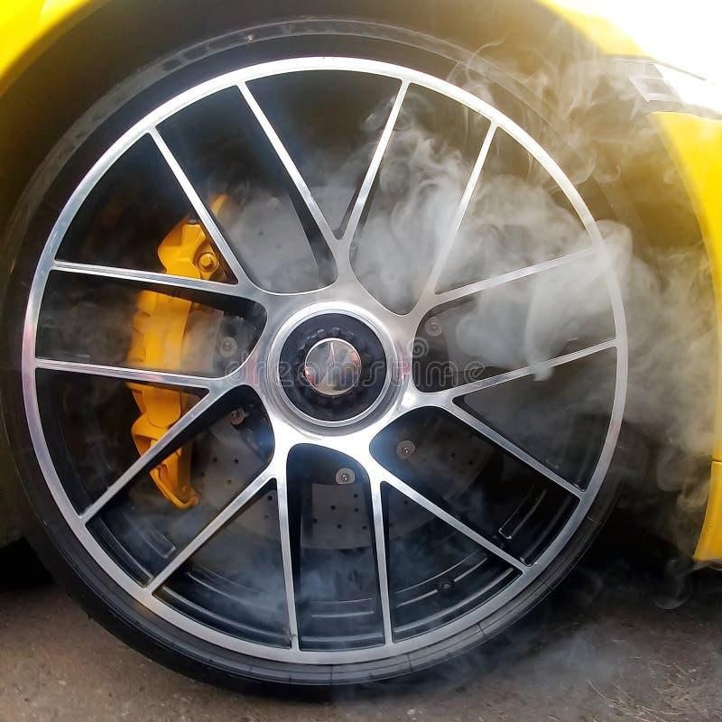 Coche amarillo con las ruedas de la aleación ligera con los frenos de cerámica del carbono y humo de él Cerca para arriba, imagen imagenes de archivo
