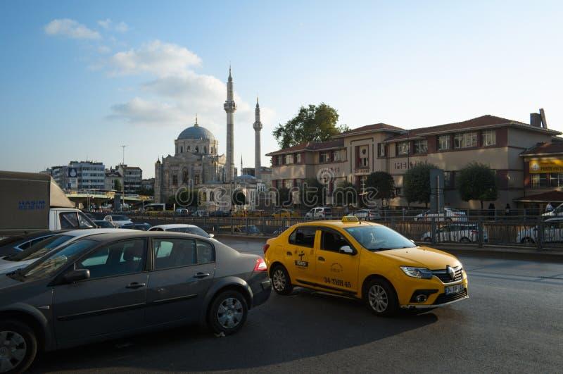Coche amarillo del taxi en el camino en un fondo de la mezquita foto de archivo