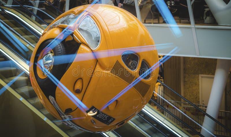 Coche amarillo machacado que cuelga dentro del centro comercial imagen de archivo
