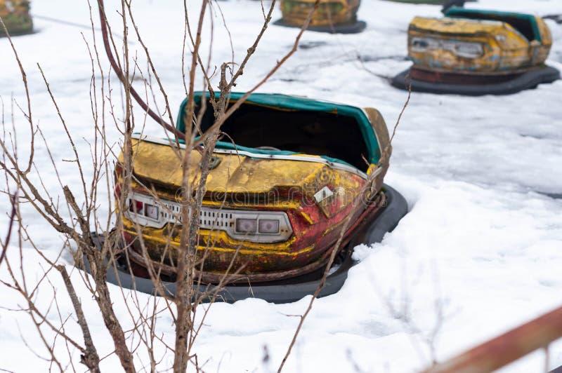 Coche amarillo oxidado de la atracción en la nieve blanca en parque de atracciones abandonado fotografía de archivo