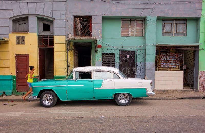 Coche americano clásico, muchacha no identificada y escena colorida de la calle en La Habana, Cuba foto de archivo libre de regalías