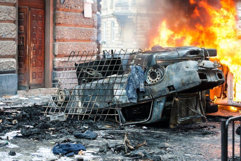 Coche ardiente coche destruido y fijado en el fuego durante los alborotos Centro de ciudad imagen de archivo libre de regalías