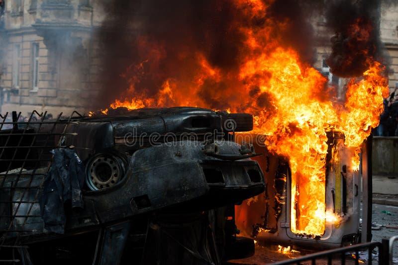 Coche ardiente coche destruido y fijado en el fuego durante los alborotos Centro de ciudad fotografía de archivo