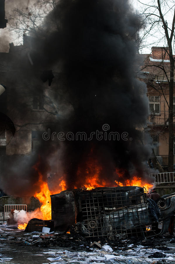 Coche ardiente coche destruido y fijado en el fuego durante los alborotos Centro de ciudad imagen de archivo