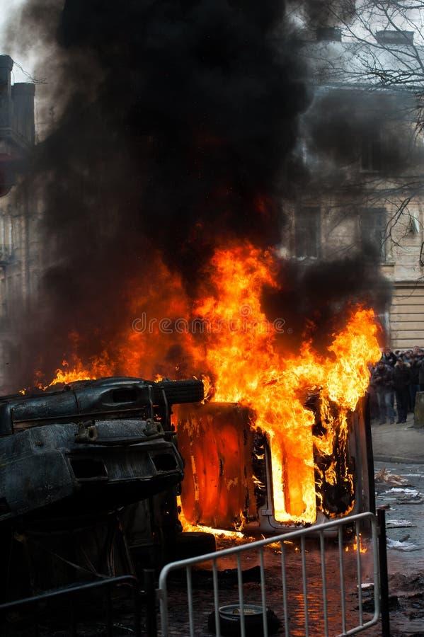 Coche ardiente coche destruido y fijado en el fuego durante los alborotos Centro de ciudad imagenes de archivo