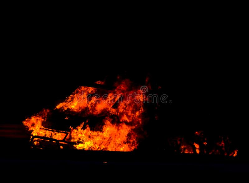 Coche ardiente en el camino en la noche, una conclusión del accidente trágico con fotos de archivo