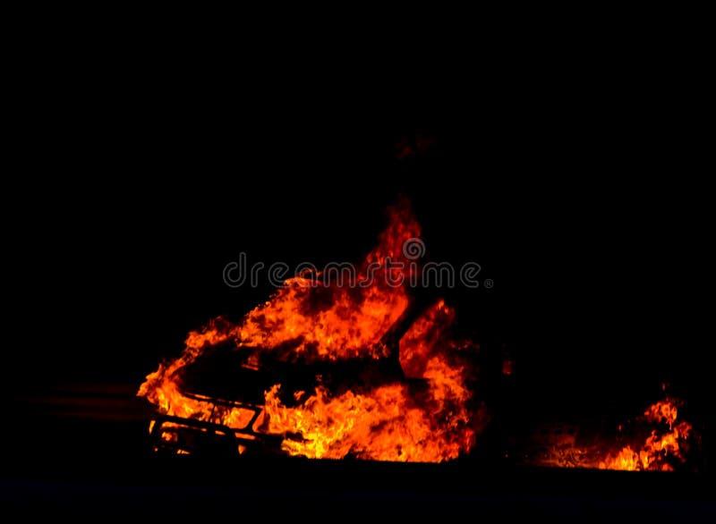 Coche ardiente en el camino en la noche, una conclusión del accidente trágico con fotografía de archivo