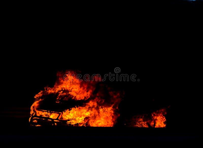 Coche ardiente en el camino en la noche, una conclusión del accidente trágico con imagenes de archivo