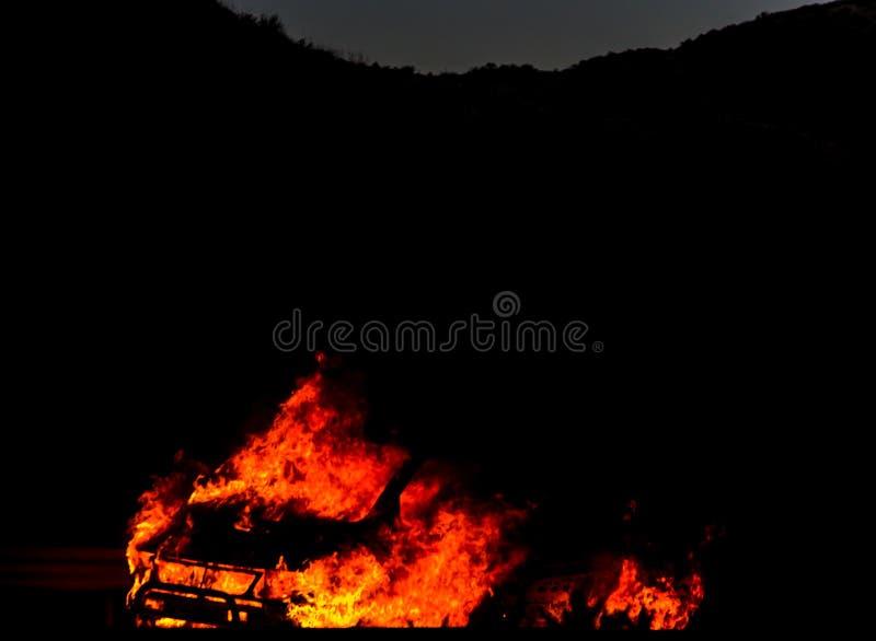 Coche ardiente en el camino en la noche, una conclusión del accidente trágico con fotos de archivo libres de regalías
